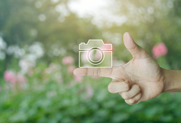 Camera flat icon on finger over blur pink flower and tree in park, Business camera service shop concept