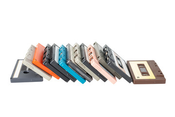 Cassette tapes stack leaning in horizontal line . Obsolete technology of audio recording and playback format audio cassette tape isolated on white background with clipping path.