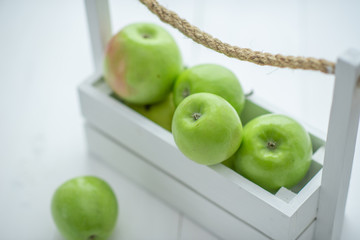 fresh green apples in a box on white background