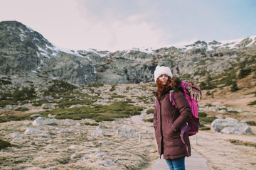 brunette girl with a hat on her head and a travel backpack contemplates the landscape that surrounds her from a valley next to the mountains