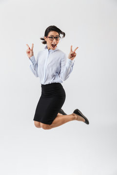 Full length portrait of a pretty businesswoman jumping