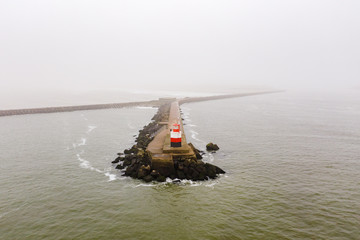 A pier with a light house at the end at the coast of the North Sea in the Netherlands.