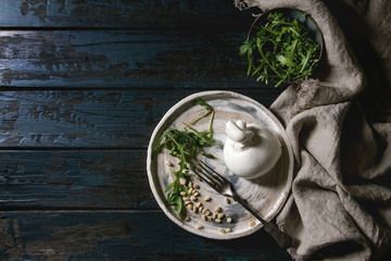 Italian burrata cheese, fresh arugula salad, pine nuts and olive oil in white ceramic plate on cloth over dark wooden plank background. Flat lay, space