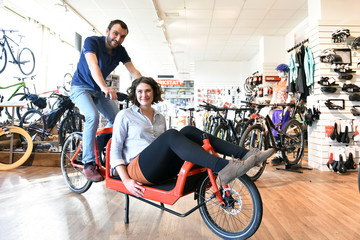 customer and dealer in bicycle shop - purchase and repair of bicycles - couple testet a transport bicycle