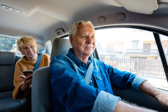 Senior uber driver sitting in a car with female passenger