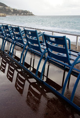 The famous blue chairs along the coast of Nice, France, after rain