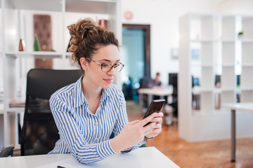 Beautiful young office worker texting on smart phone.