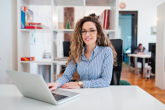 Portrait of confident young businesswoman in formal wear sitting at workplace, looking at camera.