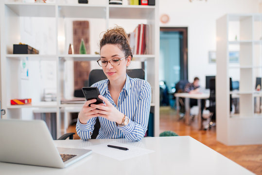 Beautiful young businesswoman texting on smart phone.