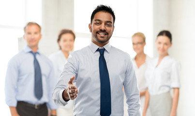 business, office worker and people concept - smiling indian businessman stretching hand out for handshake over colleagues on background