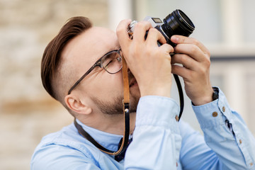 photography, technology and lifestyle - young photographer or hipster man with vintage film camera outdoors