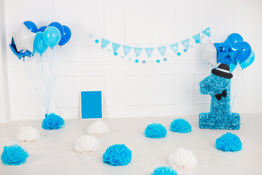 White room decorated with blue decor for first baby boy birthday celebration. Horizontal color photography.
