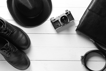 Stylish male accessories and photo camera on white wooden background