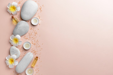 Spa composition with stones, flowers and candles on light background