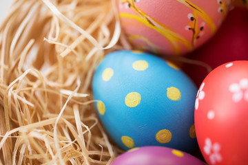 easter, holidays, tradition and object concept - close up of colored eggs in straw