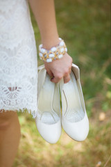 Closeup view of beautiful caucasian woman holding pair of white high heels in hands while standing outdoors. Vertical color photography.