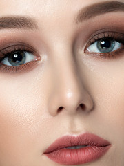 Close up beauty portrait of young woman with beautiful fashion makeup. Brown smokey eyes. Studio shot. Extreme closeup, partial face view