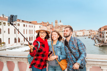 Happy group of friends travelers making selfie with selfie stick at the background of the Grand Canal in Venice, Italy