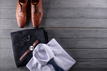 Stylish men's clothes with accessories on wooden background