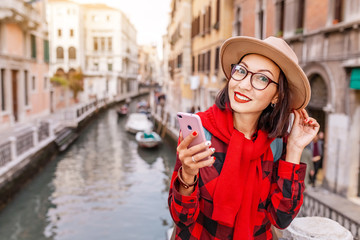 Young happy asian traveler woman with smartphone on the pier of a narrow canal and street in Venice. Vacation in Italy concept
