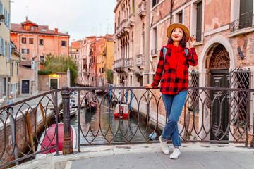 Young happy asian traveler woman on the pier of a narrow canal and street in Venice. Vacation in Italy concept