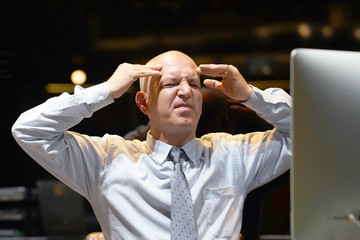Close-up of an office worker. Elderly man in stress in front of a computer. Poor economy concept. Face expression, emotion