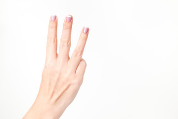 Closeup view of female hand showing three fingers isolated on white background. Fingernails with beautiful french pink manicure. Horizontal color photography.