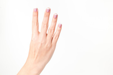 Closeup view of female hand showing four fingers isolated on white background. Fingernails with beautiful french pink manicure. Horizontal color photography.