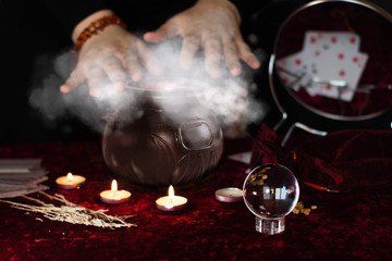 Hands over the magic cauldron. Cooking magic potion. Magic crystal ball and candles on the table.