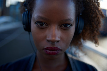 Beautiful black woman wearing headphones in urban city setting during sunrise
