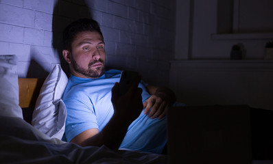 Man using smartphone, surfing net late at night