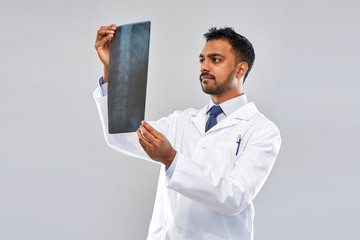 medicine, healthcare and people concept - indian doctor looking at spine x-ray over grey background