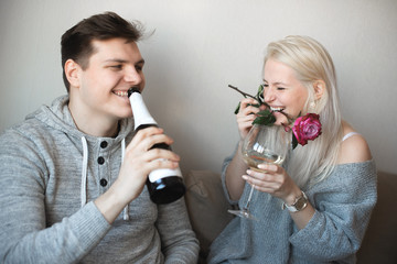 Love is a great feeling. Celebrating anniversary. Young loving couple sitting close to each other hugging and drinking white wine