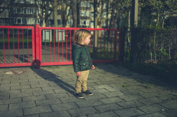 Little toddler standing by gate in park