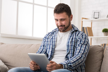 Young man reading online article on digital tablet