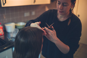 Woman cutting friend's hair in kitchen