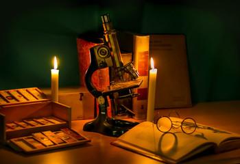 Historisches Mikroskop Stilleben mit Buch, Brille und Kerzenlicht. Geschichte der Mikroskopie Wissenschaft
