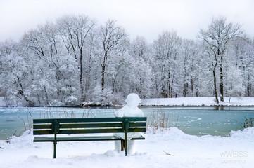 Schneemann sitzt auf Bank im Park mit See im Winter, Geduld Warten