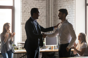 Excited black boss handshake male employee greeting with success