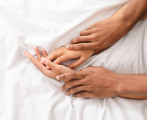 Man and woman hands having sex on bed