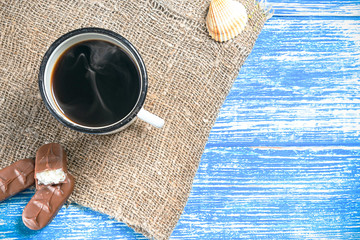 Blue aged wooden background for billets and design with old cloth from the bottom and a cup of fragrant coffee with a chocolate bar