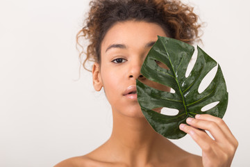 Woman with tropical leaf covering half of face
