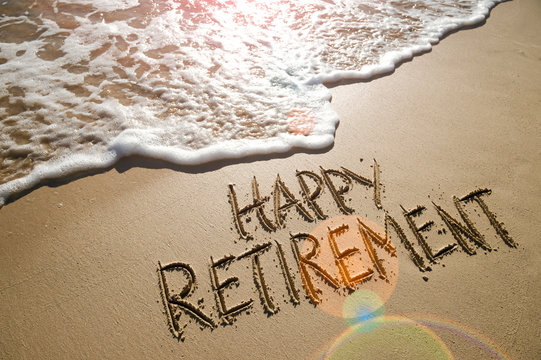 Happy Retirement message handwritten on smooth sand beach with gentle wave
