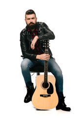 handsome male musician in black leather jacket posing with acoustic guitar, isolated on white