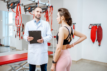 Young woman during the medical consultation with senior physiotherapist at the rehabilitation office with suspension medical equipment
