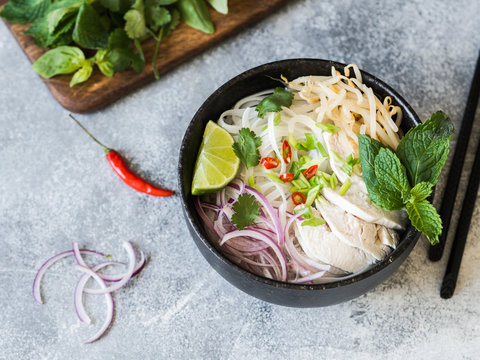 Traditional Vietnamese soup- pho ga in black bowl with chicken and rice noodles, mint and cilantro, green and red onion, chili, bean sprouts and lime on grey background. Asian food.