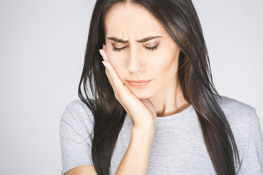 Young European woman isolated on white background suffering from severe toothache, feeling pain so strong that she is pressing fingers to cheek to calm it down, looking desperate.