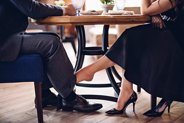 Girl flirts with a guy in a restaurant. She touches his leg with her bare foot under the table