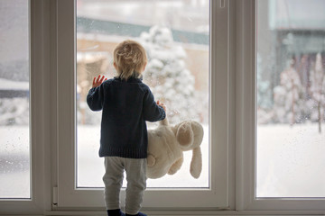 Toddler child standing in front of a big french doors, leaning against it looking outside at a snowy nature .