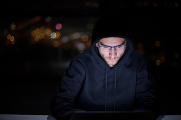 hacker using laptop computer while working in dark office